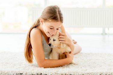 Emotional girl hugging retriever puppy