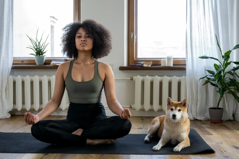 Woman sitting on mat doing yoga with her dog beside her