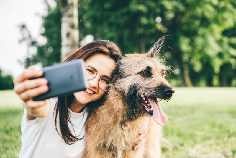 Woman taking a selfie of her and dog