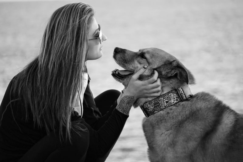 Black and white image of woman looking into eyes of a dog